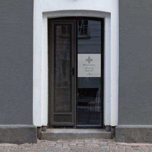 naklejka matująca na drzwi z logiem kancelarii notarialnej i godzinami otwarcia